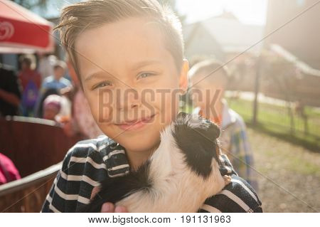 Portrait of happy smiling boy with cavy. Sunny day.