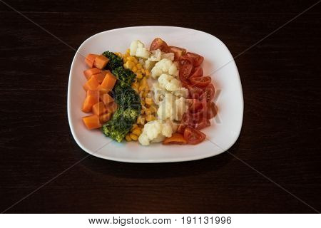 Boiled carrot broccoli corn cauliflower tomato on white plate. Concept. Healthy food. Low-Carb Diet. Vegetarian food.