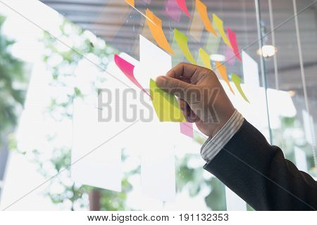 Businessman Look At The Adhesive Notes On Glass Wall In Meeting Room. Sticky Note Paper Reminder Sch