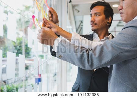Business Team Look At The Adhesive Notes On Glass Wall In Meeting Room. Sticky Note Paper Reminder S