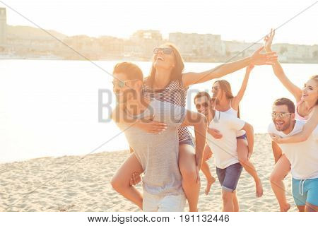 Freedom, Love, Friendship, Summer Mood. Happy Young Boyfriends Piggybacking Their Girlfriends At The