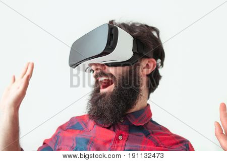 Young bearded man in checkered shirt laughing in VR goggles isolated on white.