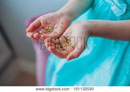 Little girls hands covered with gold glittering stars. Christmas, birthday, party time.