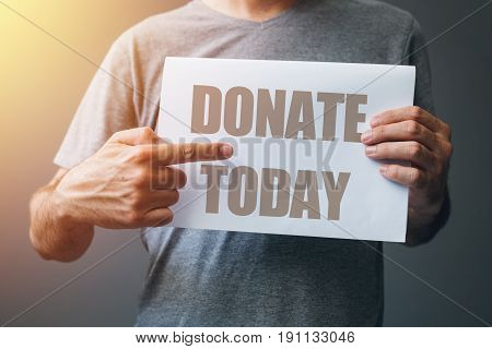 Man holding Donate today poster finger pointing to text