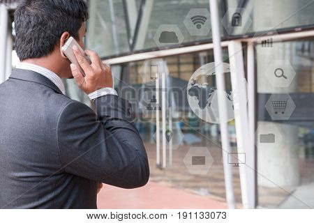Businessman In Suit Talking On Smart Phone While Standing Outside Building. Young Asian Male Using C