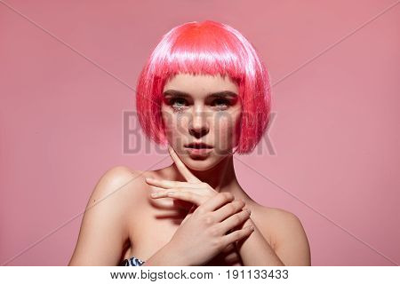 Young stylish woman wearing pink wig looking at camera and touching chin on the pink background.