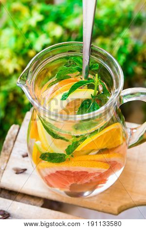 Glass pitcher with detox infused citrus water with grapefruits oranges limes lemons fresh mint wooden garden fruit box green plants authentic atmosphere cleansing