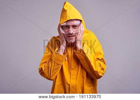 A middle aged man in a yellow raincoat and safety glasses feeling frightened