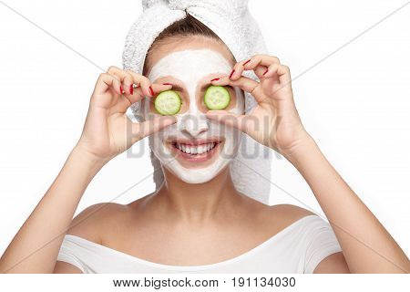 Young smiling woman with towel on head and mask on face holding cucumber slices covering eyes.