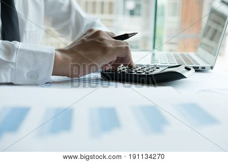 Young Businessman Working With Calculator, Business Document And Laptop Computer Notebook In Office.