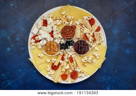Cheese assorti with sauces and popcorn top view blue background