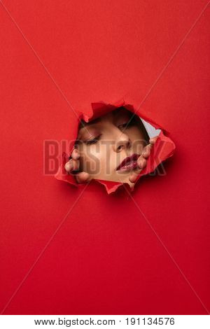 Model standing behind sheet of red cardboard tearing it with hands.