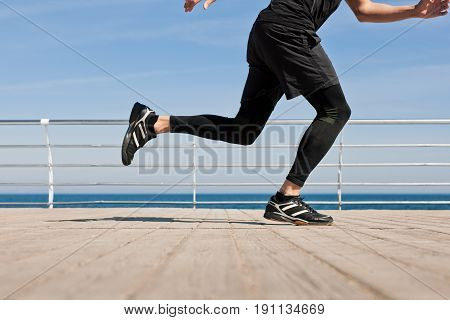 Crop side view of sportsman running on wooden pier with sea on background.