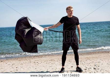 Fit man standing with a parachute for running on the beach. Horizontal outdoors shot.