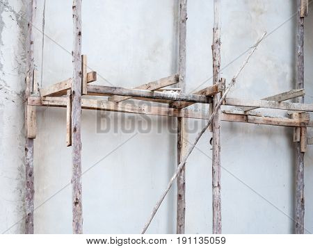 Old wooden scaffolding for use in the unfinished building of the urban area.
