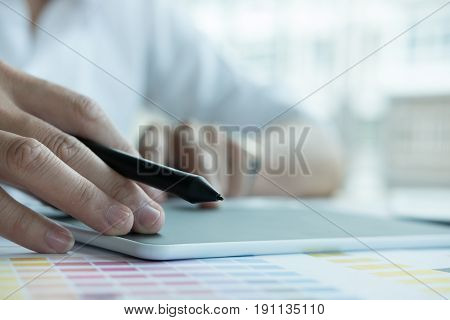 Young Graphic Designer Working With Color Swatch. Creative Man Using Stylus Pen And Digital Tablet A