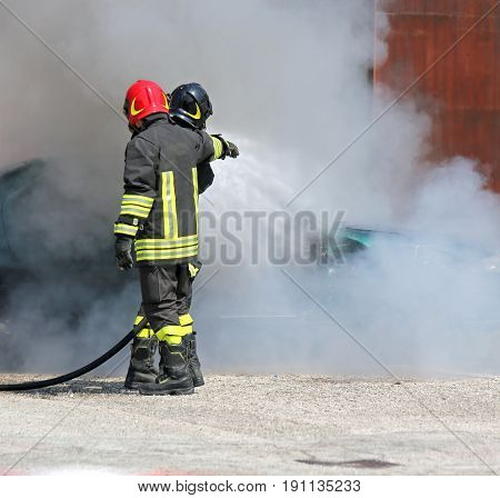 Firefighters With Uniform And Protective Helmet Extinguish The F