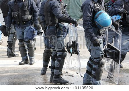 Policemen In Riot Gear With Hardhat While Patrolling The Streets