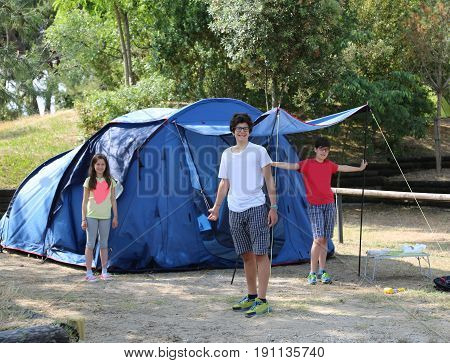 Three smiling children mount the tent in the campsite during summer vacation
