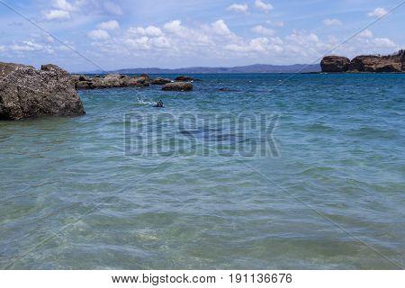 Calm water in Rajada Beach with a man snorkeling near the rocks.