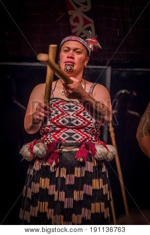 NORTH ISLAND, NEW ZEALAND- MAY 17, 2017: Close up of a Tamaki Maori woman with traditionally tatooed face and wearing traditional dress at Maori Culture village holding a wooden sticks in Tamaki Cultural Village, Rotorua, New Zealand.