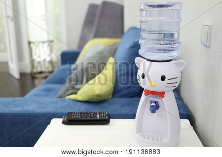 MOSCOW - JAN 20, 2017: Childrens cooler in the form of a toy with a bottle of water on the table in front of the sofa in the room