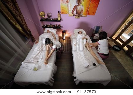 MOSCOW - JAN 30, 2017: Two Tahitian women (with model release) doing massage for a woman and a man (with model release) in a spa salon, wide angle, top view