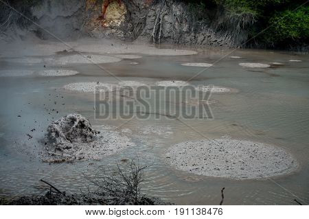 Mud texture or wet dark soil as natural organic clay and geological sediment mixture. Boiling hot mud in Waitapu, North Island in New Zealand.