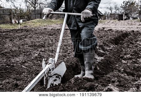 A man holding a metal plow. He was a plow plowing the land.