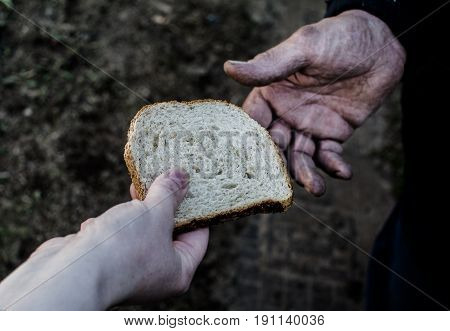 Woman giving a piece of bread grown man. From hand to hand.