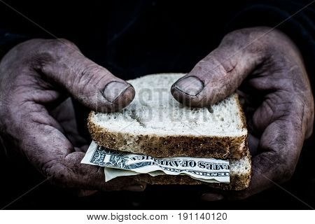 Men hands hold two pieces of bread and money.