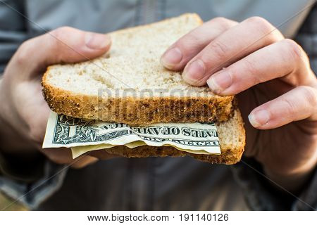 Woman's hand holding two pieces of bread and money.