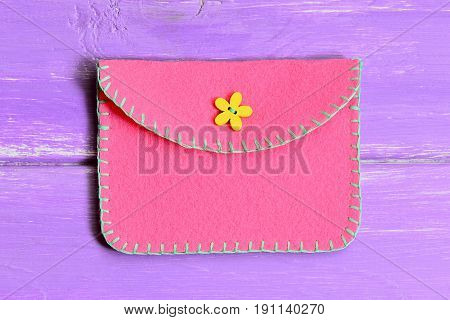 How to make a simple felt purse. Step. Quick and easy sewing crafts instruction. Handmade pink felt purse isolated on wooden background. Top view