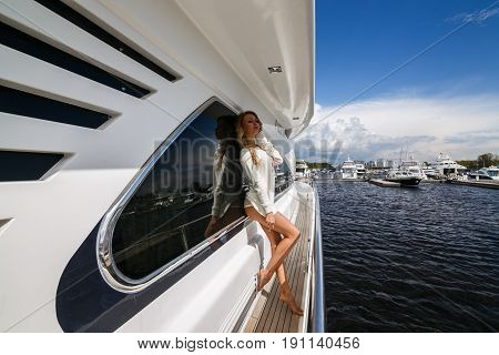 Beautiful sexy blonde girl posing on yacht, ship, boat