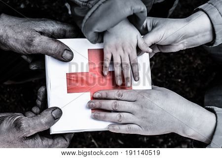 Male hands, female hands and child's hands holding a box. On the box the image of the red cross.