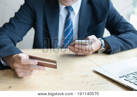 Male Holding A Credit Card And Using Laptop Computer For Online Shopping. Businessman Purchase Goods
