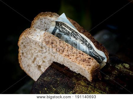 Two pieces of bread with the money Clamped in a metal vise.