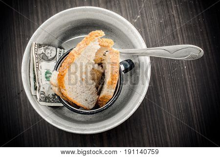 Two pieces of bread with the money in a metal plate.