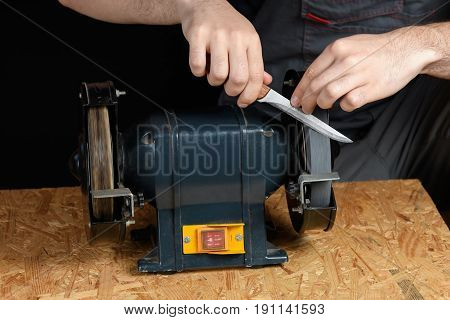 Man In Working Clothes On A Professional Sharpening Machine Kitchen Knife On A Carpenter's Workbench