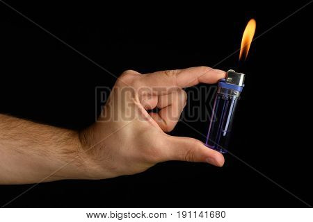 Male Hand Holding A Purple Lighter In The Fingers With A Large Flame On A Black Background Rich Colo