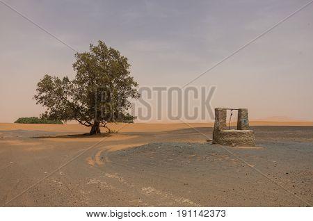 Draw-well In Merzouga Village Near Sahara Erg Chebbi  Dune In Sand Storm. Morocco
