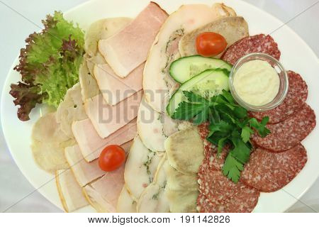 Plate with sliced meat on a celebratory table