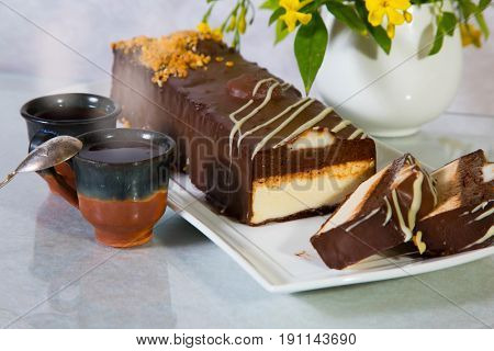 Delicious cheesecake with white and brown chocolate. The background is cup with hot tea and vase with flowers. Professional bakery
