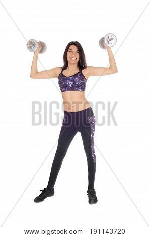 A young Hispanic woman in an exercising outfit standing isolated for white background holding two heavy dumbbells up.