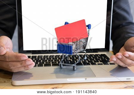 Male Showing A Credit Card In Mini Supermarket Cart Trolley Full Of Coins On Laptop Computer For Onl