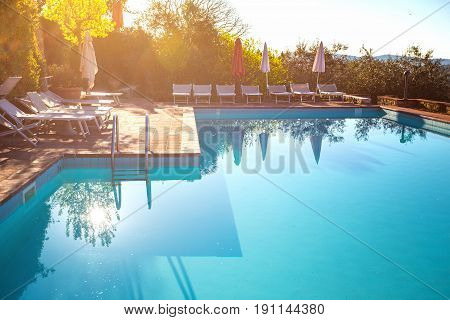 Swimming pool and chaise-longue with umbrella morning at dawn tuscany italy