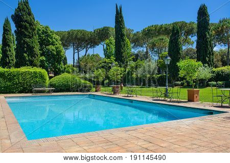 Swimming pool and cypresses, sunny day without people