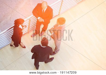 Businessmen and businesswoman standing together by railing