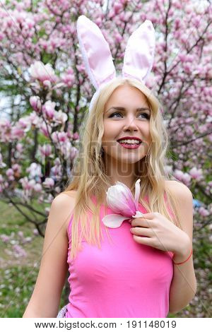 easter girl. girl in bunny ears with magnolia branch near blossoming tree