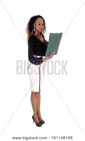 A beautiful young African American woman standing in full length and reading her reports isolated for white background.
